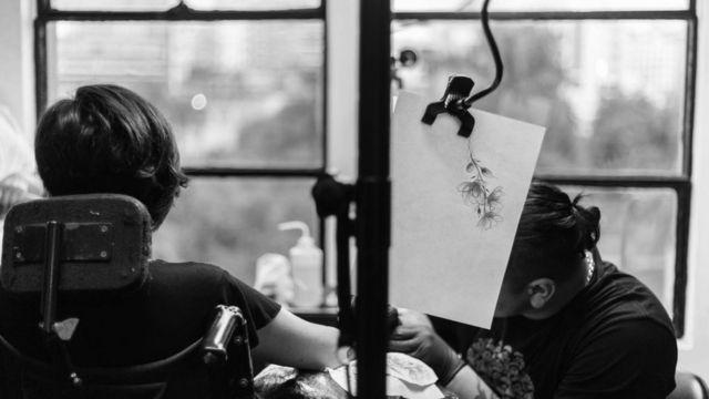 Ana Estrada siendo tatuada en un brazo.