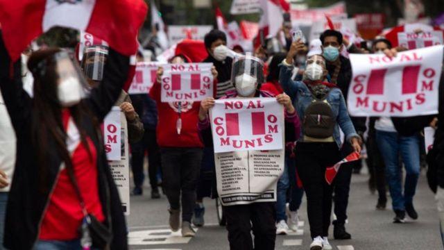 """Detractores de Pedro Castillo protestan con pancartas que dicen """"no al comunismo""""."""